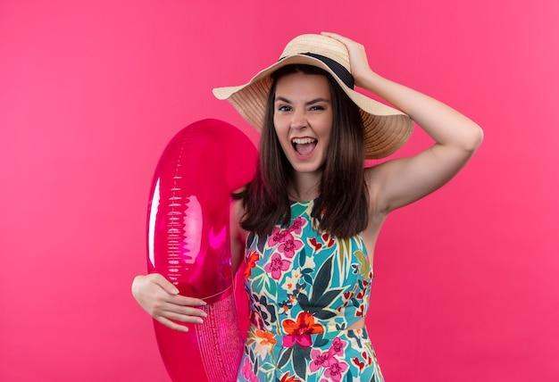 Mujer joven confiada con sombrero sosteniendo el anillo de natación y poniendo la mano en la cabeza en la pared rosa aislada