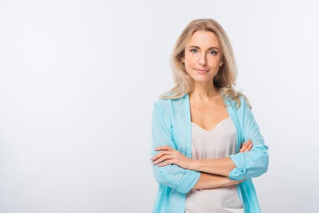 Mujer joven confiada sonriente que se coloca con sus brazos cruzados contra el contexto blanco