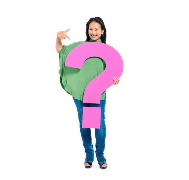 Mujer joven confiada sosteniendo y señalando signo de interrogación