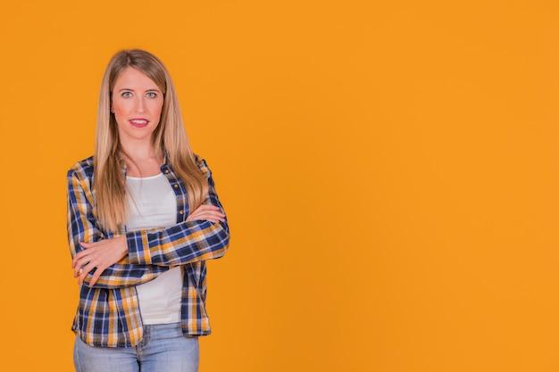Mujer joven confiada con su brazo cruzado mirando a la cámara