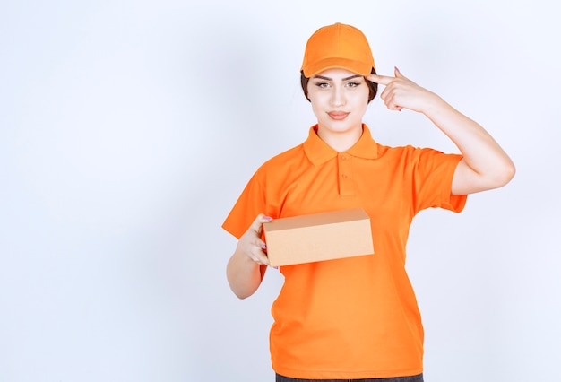 Mujer joven confiada en unishape sosteniendo su dedo en la cabeza mientras sostiene la caja