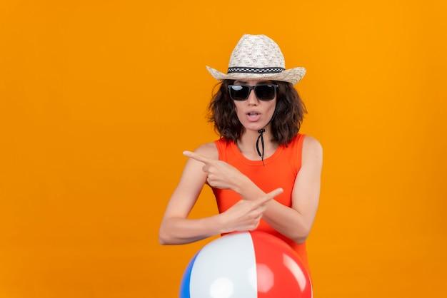 Una mujer joven confundida con el pelo corto en una camisa naranja con sombrero para el sol y gafas de sol sosteniendo una bola colorida inflable