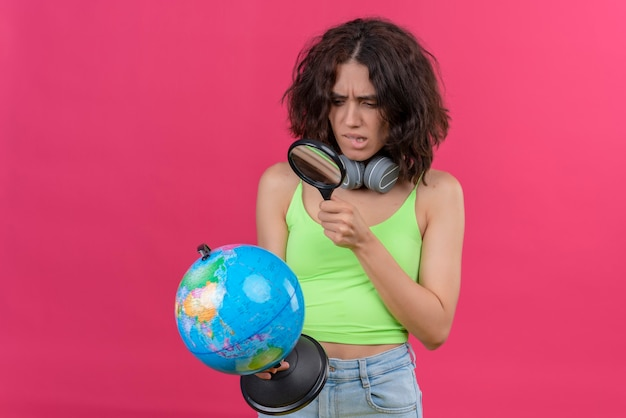 Una mujer joven confundida con el pelo corto en la parte superior de la cosecha verde en auriculares mirando el mundo con lupa