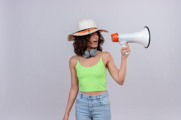 Una mujer joven confundida con el pelo corto en la parte superior de la cosecha verde en auriculares con sombrero para el sol mirando sorprendentemente un megáfono sobre un fondo blanco.
