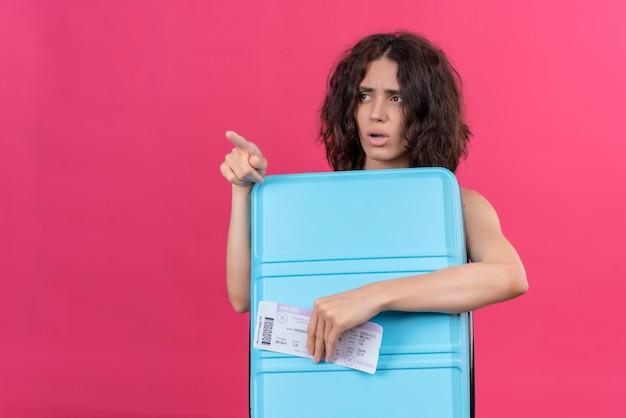 Una mujer joven confundida con pelo corto vistiendo verde crop top apuntando con el dedo índice sosteniendo la maleta azul con billetes de avión