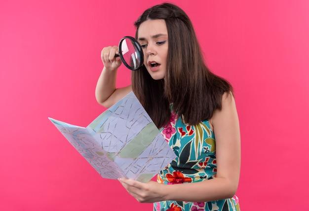 Mujer joven confusa que sostiene el mapa y el vidrio de la lupa en la pared rosada aislada