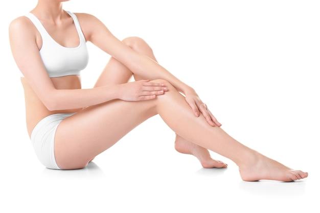 Mujer joven, conmovedor, ella, pierna, blanco