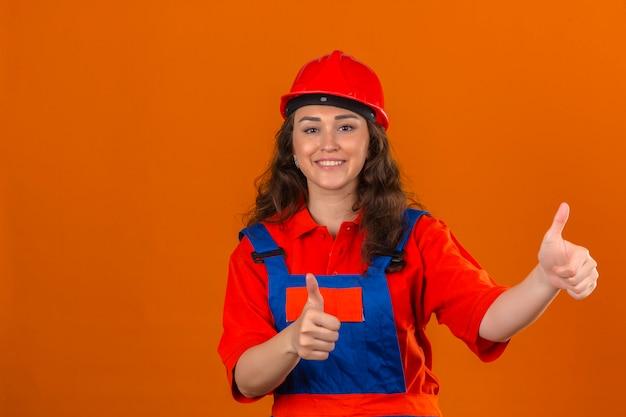 Mujer joven constructor en construcción uniforme y casco de seguridad mostrando pulgares arriba sonriendo alegremente sobre pared naranja aislada