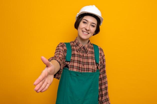 Mujer joven constructor en uniforme de construcción y casco de seguridad mirando sonriendo amable ofreciendo mano haciendo gesto de saludo