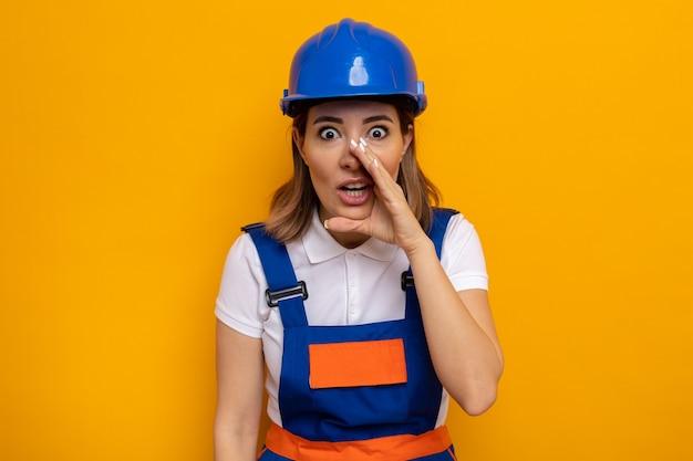 Mujer joven constructor en uniforme de construcción y casco de seguridad mirando sorprendido diciendo un secreto sosteniendo la mano sobre la boca