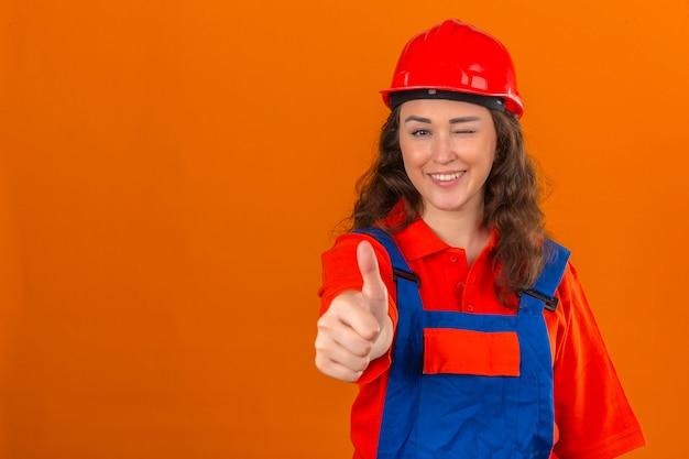 Mujer joven constructor en uniforme de construcción y casco de seguridad mostrando pulgares arriba sonriendo alegremente guiñando un ojo sobre la pared naranja aislada