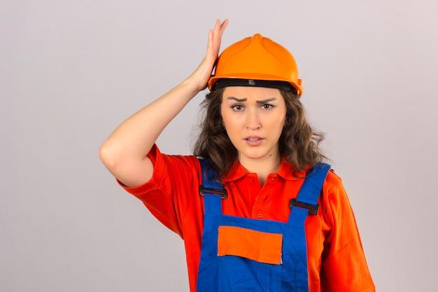 Mujer joven constructor en uniforme de construcción y casco de seguridad de pie sorprendido con la mano en la cabeza por error concepto de mala memoria sobre la pared blanca aislada