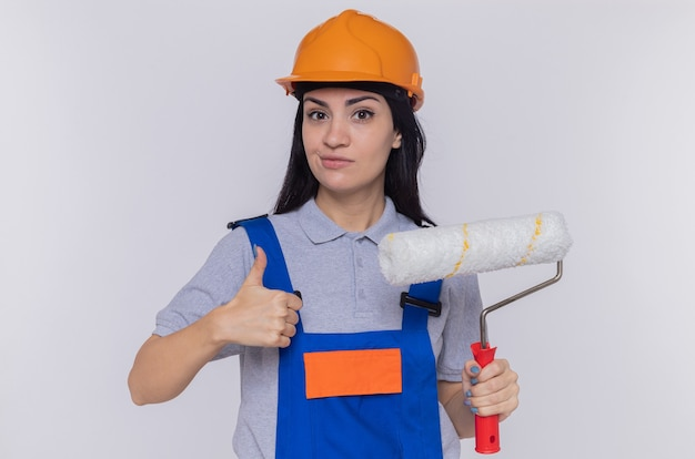Mujer joven constructor en uniforme de construcción y casco de seguridad con rodillo de pintura mostrando el pulgar hacia arriba sonriendo confiado de pie sobre la pared blanca