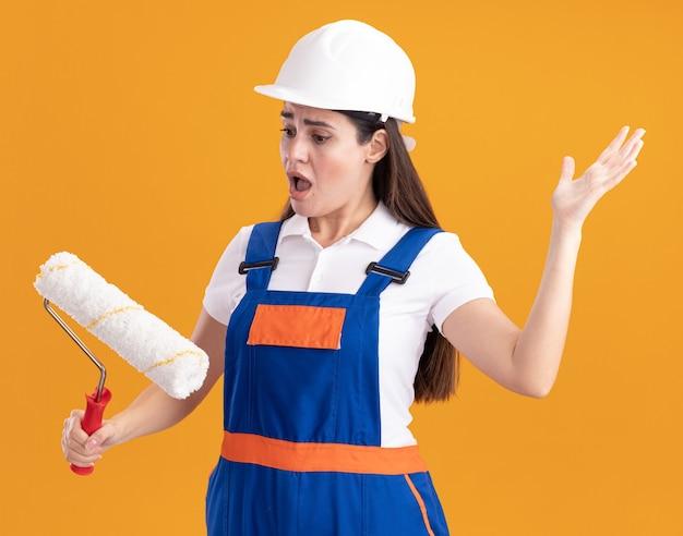 Mujer joven constructora asustada en uniforme sosteniendo y mirando el cepillo de rodillo aislado en la pared naranja