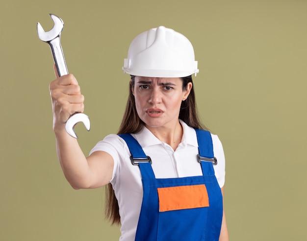 Mujer joven constructora confiada en uniforme sosteniendo una llave de boca en la cámara aislada en la pared verde oliva