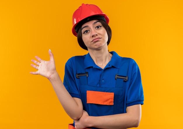 Mujer joven constructora disgustada en uniforme extendiendo la mano aislada en la pared amarilla