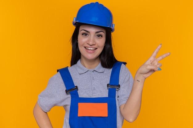 Mujer joven constructora feliz y positiva en uniforme de construcción y casco de seguridad