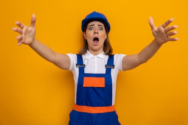Mujer joven constructora en uniforme de construcción y casco de seguridad conmocionada levantando los brazos en pánico de pie sobre la pared naranja