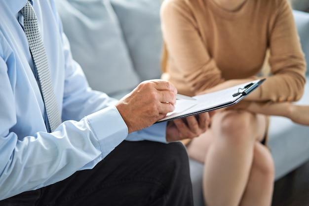 Mujer joven en una consulta con un psicoterapeuta. psicóloga teniendo sesión con su paciente en el consultorio, dándole consejos sobre su vida.