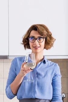 Mujer joven contemplada sonriente que sostiene la copa de vino disponible