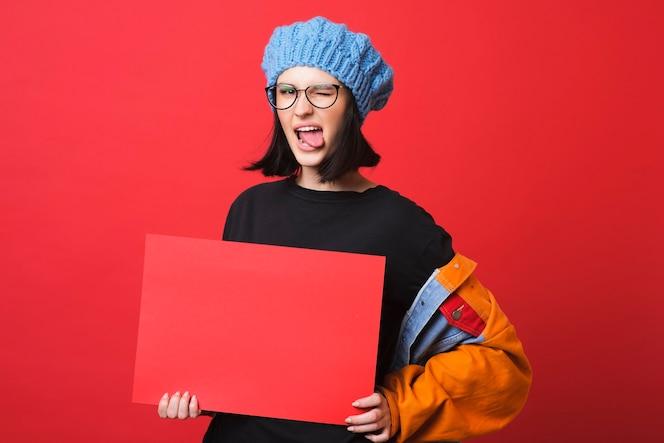 Mujer joven contemporánea en vasos mostrando la lengua mientras sostiene un cartel rojo vacío