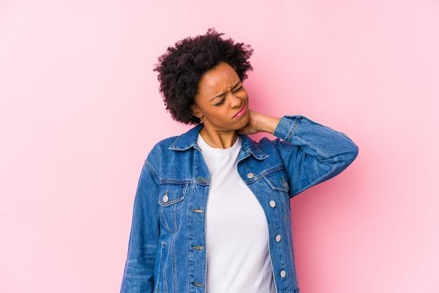 Mujer joven contra un backgroound rosado aislado que sufre dolor de cuello debido a un estilo de vida sedentario