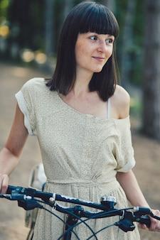 Mujer joven contra el fondo de la naturaleza con bicicleta