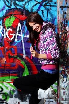 Mujer joven contra la pared con graffiti