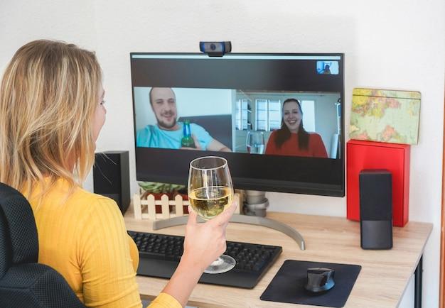 Mujer joven conversando con amigos bebiendo vino y riendo juntos