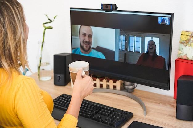Mujer joven conversando con amigos tomando café y riendo juntos