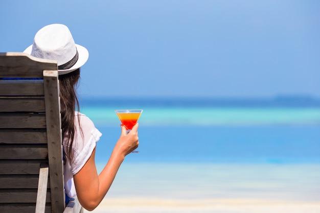 Mujer joven con copa de cóctel junto a la piscina
