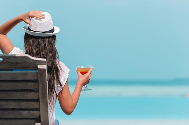Mujer joven con copa de cóctel en la playa blanca