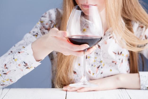 Mujer joven con una copa de vino. adicto a las drogas y al alcohol.