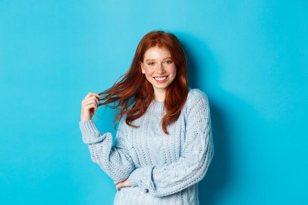 Mujer joven coqueta con el pelo rojo, jugando con el pelo y sonriendo, de pie en suéter sobre fondo azul.