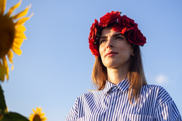 Mujer joven con una corona de flores rojas disfrutando de la puesta de sol en un campo de girasoles.