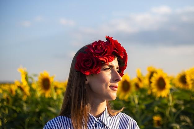 Mujer joven con una corona de flores rojas mira hacia la puesta de sol en un campo de girasoles.