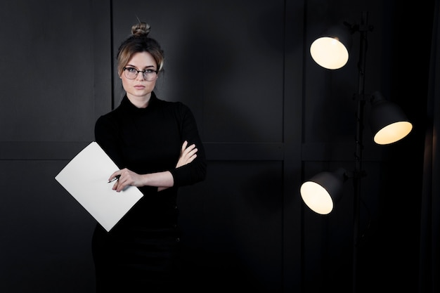 Mujer joven corporativa con anteojos con papeles