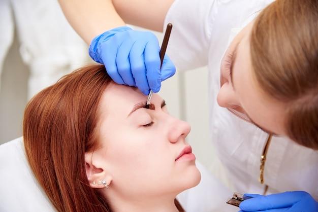 Mujer joven en corrección de cejas en clínica de cosmetología.
