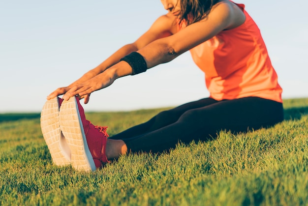 Mujer joven corredor estirando las piernas antes de correr en la hierba.