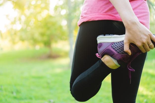 Mujer joven del corredor que estira las piernas antes de correr en el parque. de cerca las zapatillas de desgaste femenino.