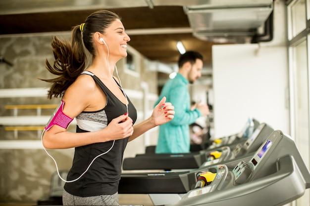 Mujer joven corriendo en la cinta y escuchando música en el gimnasio