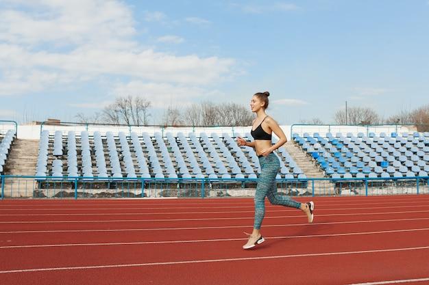 Mujer joven corriendo durante la mañana soleada en la pista del estadio