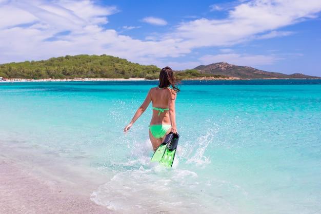 Mujer joven corriendo hacia el mar tropical azul con equipo de snorkel