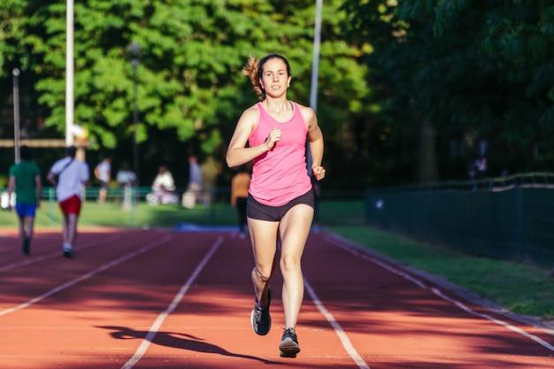 Mujer joven corriendo en la pista de la corte