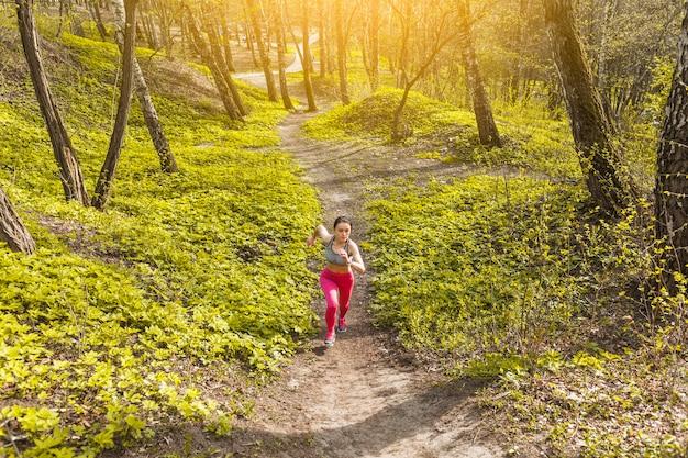 Mujer joven corriendo a través de los árboles