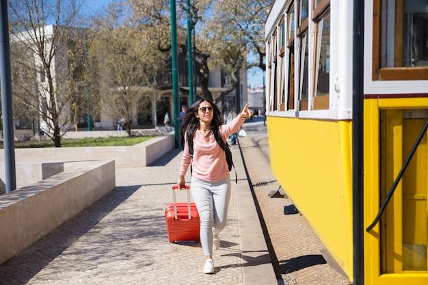Mujer joven corriendo tras un trolebús y tirando de una maleta.