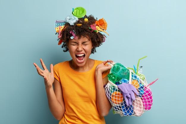 Mujer joven con corte de pelo afro sosteniendo la bolsa con residuos plásticos