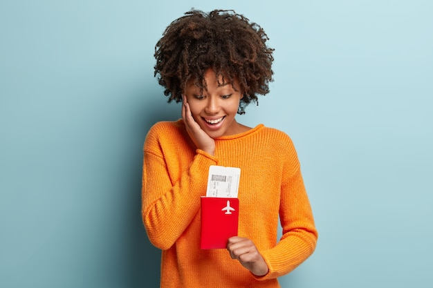 Mujer joven con corte de pelo afro vistiendo jersey naranja