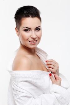 Mujer joven con corte de pelo corto en bata de baño