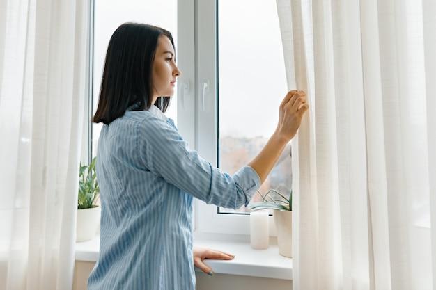 Mujer joven en las cortinas de apertura de la camisa azul que miran por la ventana por la mañana en el cuarto